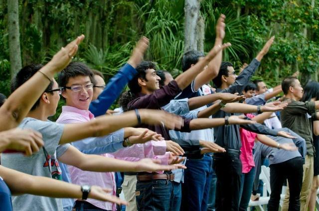 International students doing the Gator chomp at the President's International Student Reception in Fall 2013.